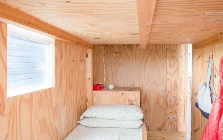 Two London Creatives Shore Up a Tiny Beach House Ikea Hack Kitchen Included The bedroom has a twin bed and a sleeping loft big enough for two. In addition to wall hooks, there are storage bins incorporated into the steps to the loft.