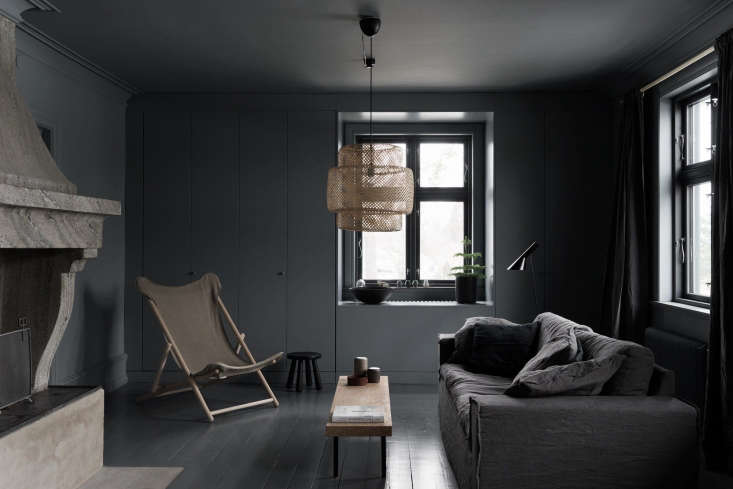 Dark gray paint surrounds the living room, from a painted wood floor to the walls and ceiling.Photography byStefan Isidor Bergkvist, courtesy ofSkälsö Arkitekter.