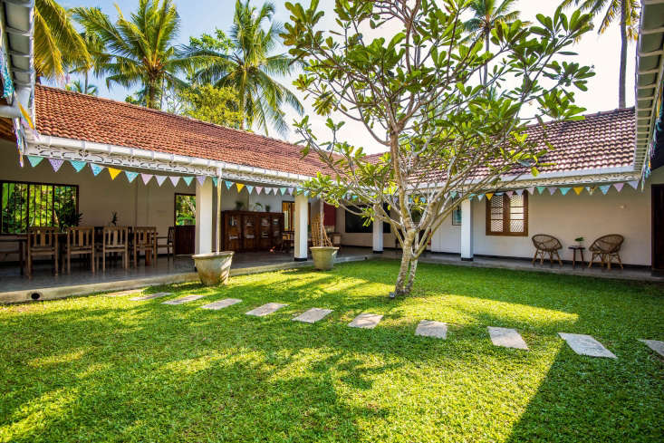 The villa is built around a grassy courtyard with a frangipani tree and has open-air dining area and living areas. Guests come from all over the world to take part in weeklong stays of organized classes and lessons. A typical day begins at 6 a.m. with yoga on the lawn &#8