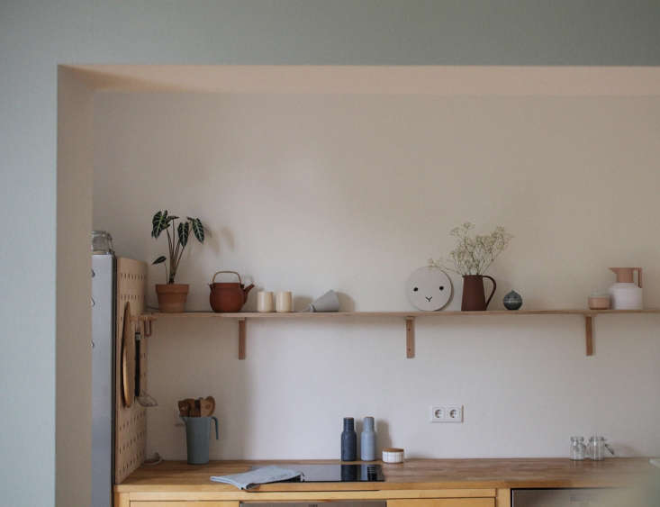 a single, diy display shelf lines the kitchen in designer and illustrator swant 14