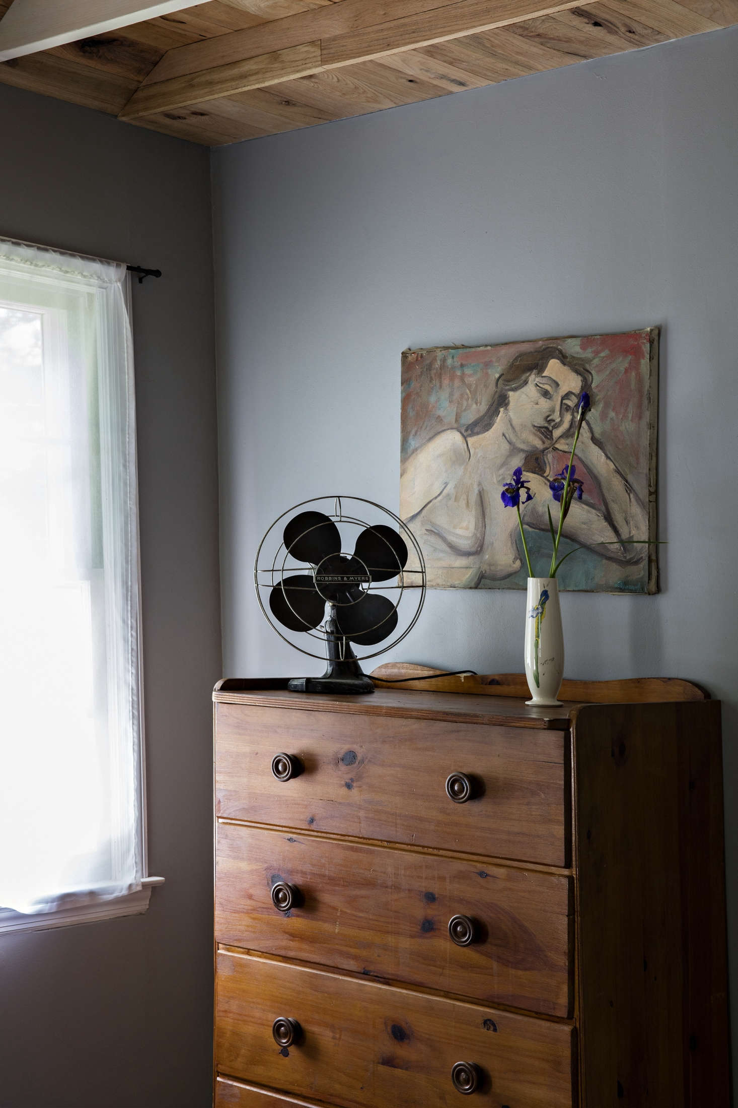Vintage fans sit atop dressers in the bungalow bedrooms.