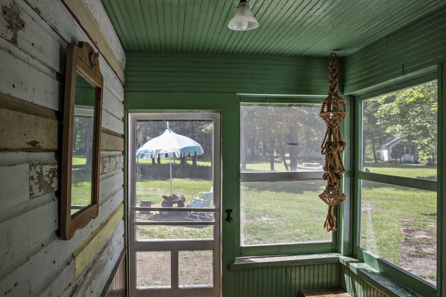A screened porch with interior cladding, painted green.
