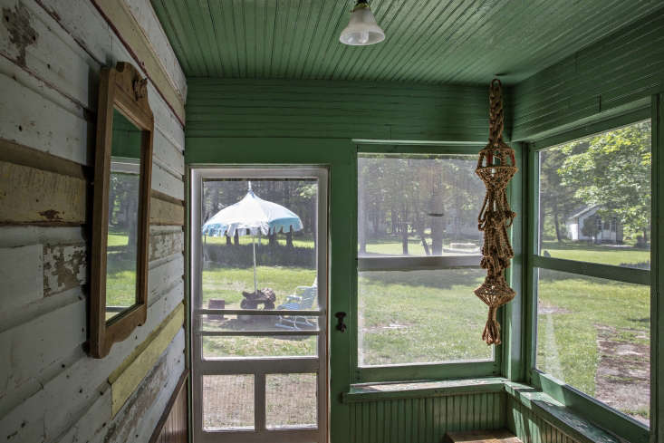 a screened porch with interior cladding, painted green. 15