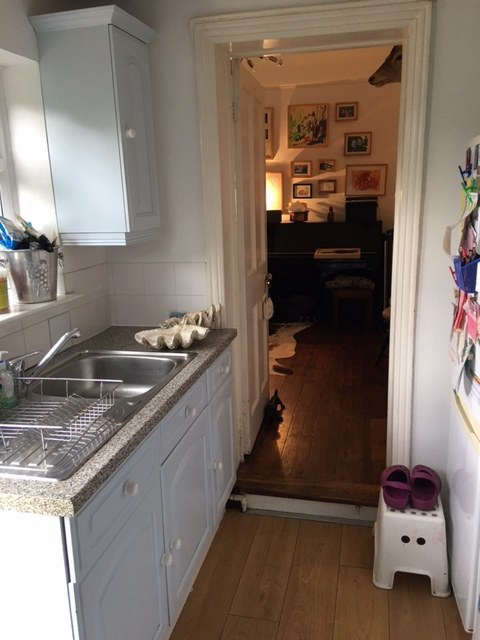 Tucked into a side addition of the house, the galley kitchen—installed decades ago as a replacement for the original kitchen—is now used as a utility room.