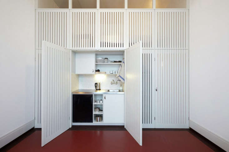 A small kitchen concealed behind slatted doors in a musician's apartment in Basel, Switzerland, designed by Buol & Zünd. Photograph by Michael Fritschi of Foto-werk.