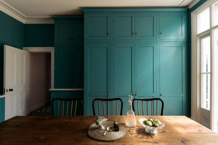 Fitted cabinets on the back wall contain a full-size refrigerator and freezer on either side of a double-door larder.