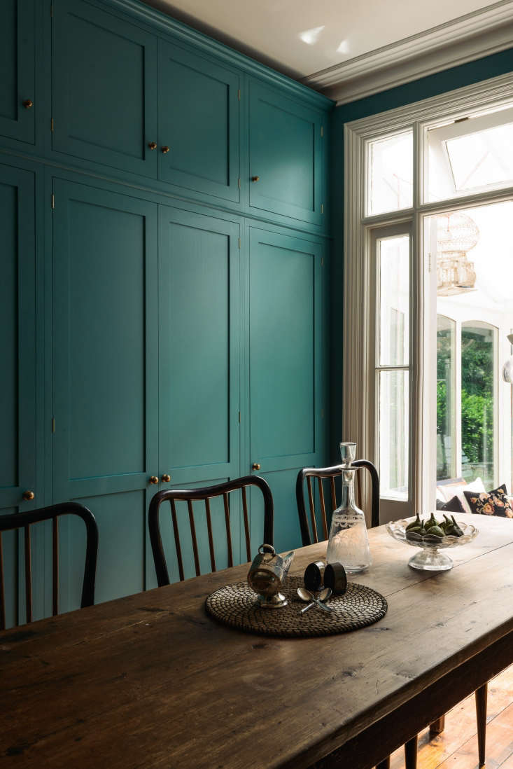 Original French doors open to a conservatory overlooking the terrace and garden.