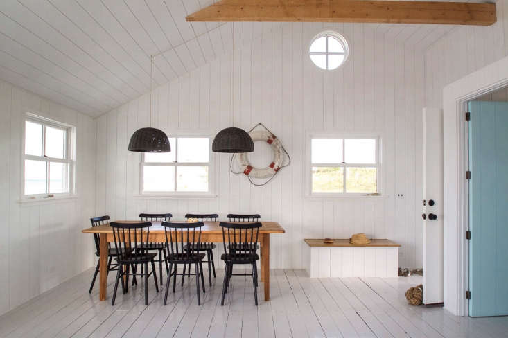 In the dining area, a suite of black Salt Chairs from Design Within Reach surrounds a Farm Table from Recycling the Past. The built-in storage bench for beach gear has a hinged lid.