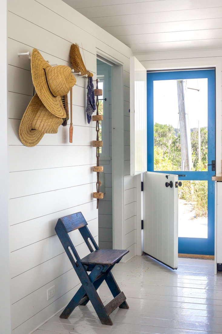 A Dutch door ushers in sea breezes (the screen door is painted in Benjamin Moore Blue Macaw high gloss); the cork buoy on the peg rail came with the original house. The floors throughout the house are painted in a California Paint high gloss finish and the interior walls and ceiling are Benjamin Moore PM-