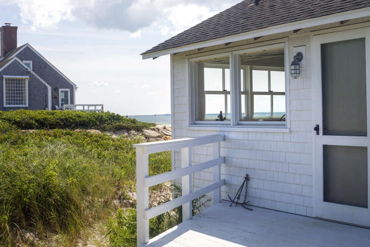 The cottage is clad in white-painted shingles; the Harbor Wallmount Light is from Urban Archaeology.
