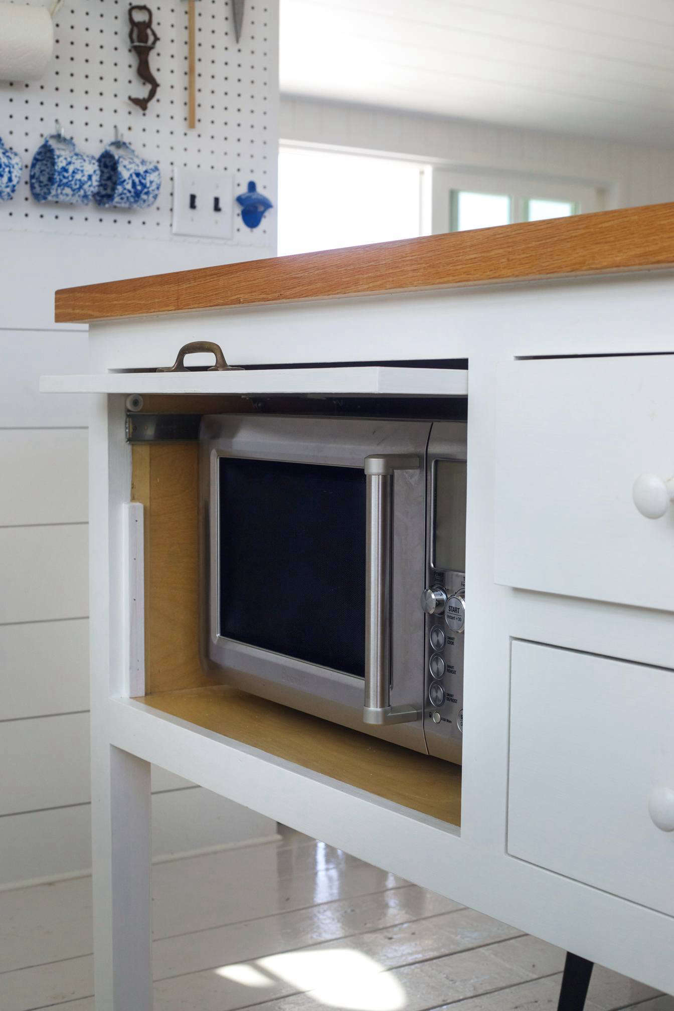 A microwaveconcealed in the kitchen island with a retractable door at the Cape Cod beach house designed byTei Carpenter andVictoria Birch. Photograph by Justine Hand fromKitchen of the Week: A Compact, Nautical Entertaining Kitchen on Cape Cod.