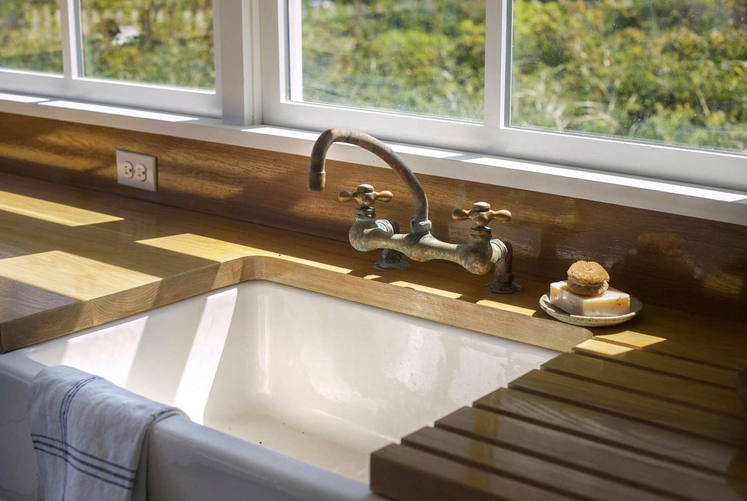 A deck-mounted utility Chicago faucet was stripped down to reveal the brass construction and paired with a ceramic farmhouse sink. (A similar sink is Shaw's 30-Inch Original 30 Fireclay Apron-Front Sink from Rohl. For more, see our post Easy Pieces: White Kitchen Farmhouse Sinks.)
