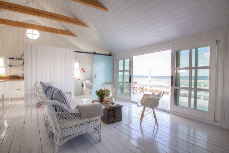 The main living area has sliding doors that open to a deck overlooking a stretch of sandy beach.