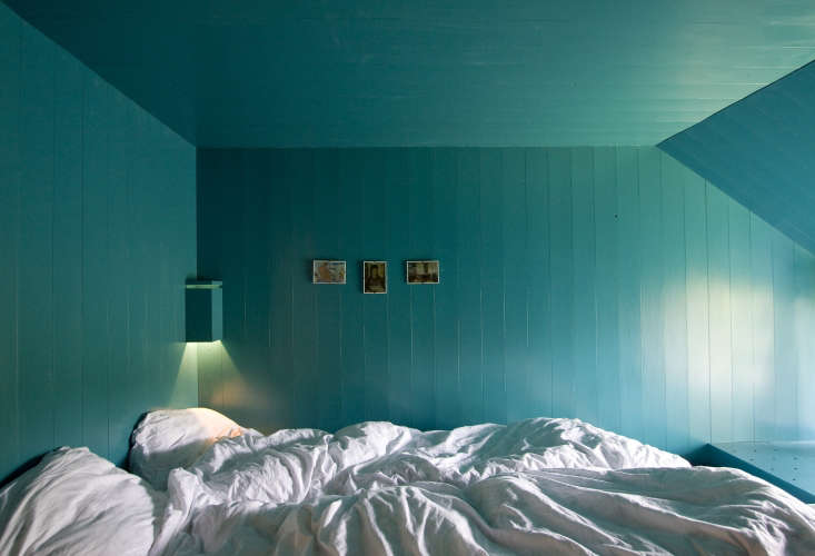 Though the bed boxes are small and intentionally dark, windows let in natural light during the day. Even the corner sconce is painted blue.