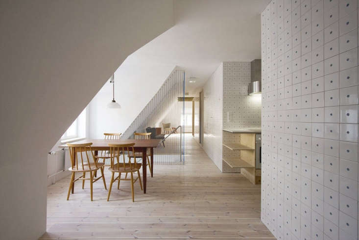 The duo started by taking down most of the interior walls to create a long, open kitchen/dining/living space, divided by a rope-lined staircase and lined in light wood.