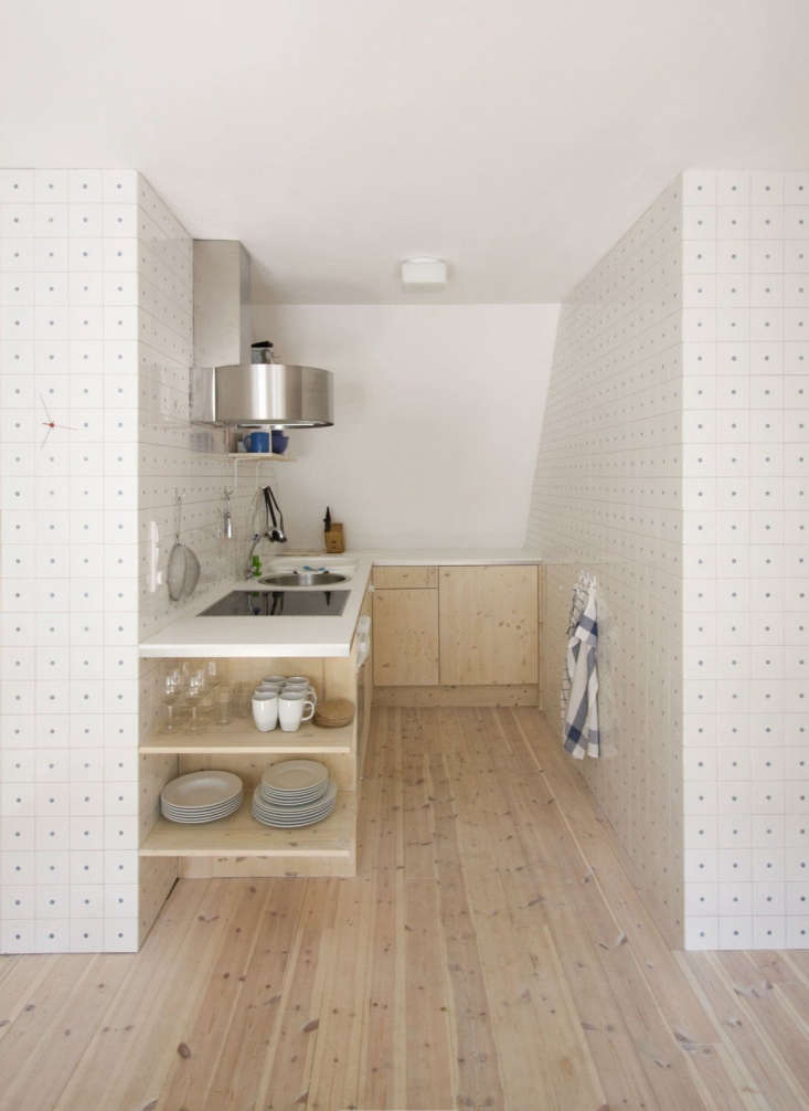 The small kitchen features pale wood cabinets with open under-counter shelving on one end.