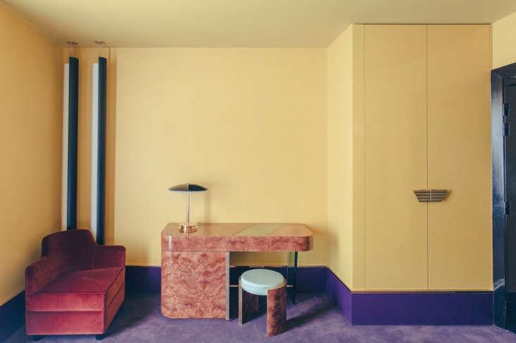 A room with wild color—purple carpet, red velvet upholstery, and pale yellow paint.