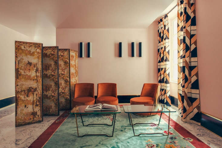 Pattern clashes that work: a vintage floral rug, custom graphic drapes, and a weathered antique screen.