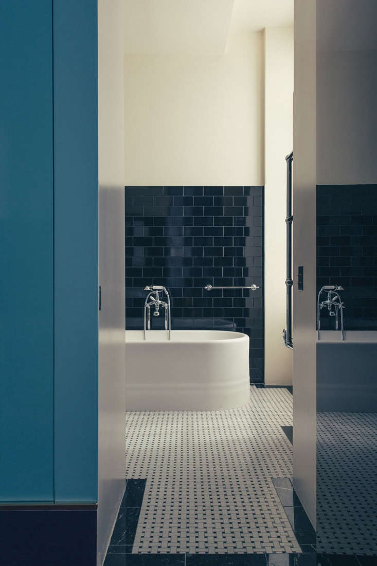 The bathroom with chrome fixtures and glossy black subway tile.