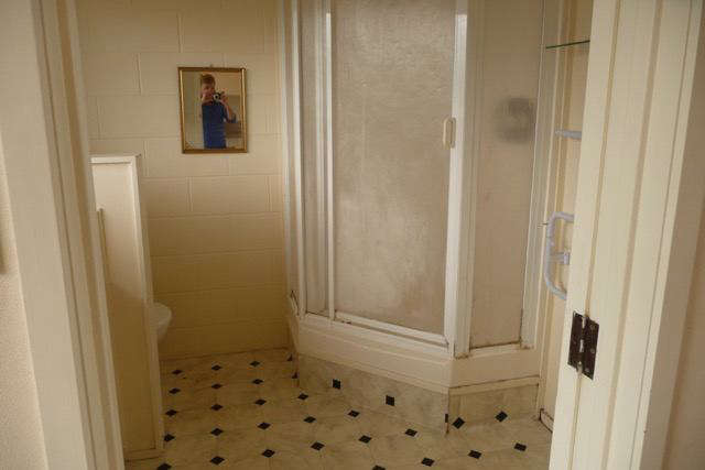 The bath, before, closed-in shower and half-wall included. Photograph courtesy of Karin Montgomery Spath.