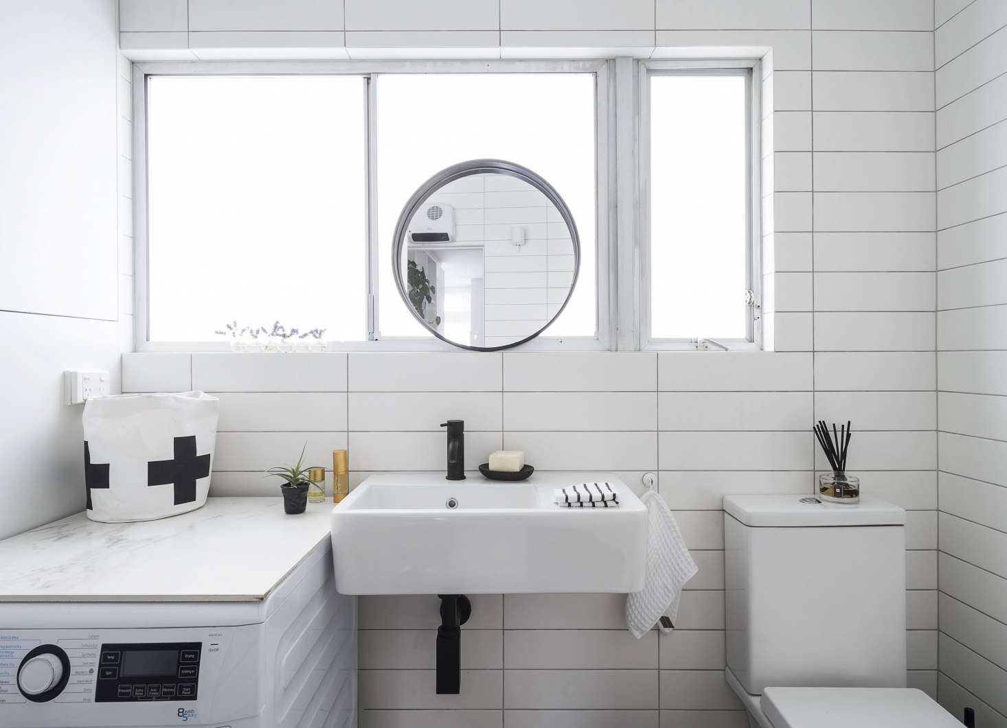 Spath removed a half-wall beside the toilet to open up the small bath. In lieu of a vanity, she sourced a wall-mounted sink (for something similar, see  Easy Pieces: Wall-Mounted Modern Square Bath Sinks), and topped the washing machine with a piece of marble from an old table that the client owned. Now it&#8