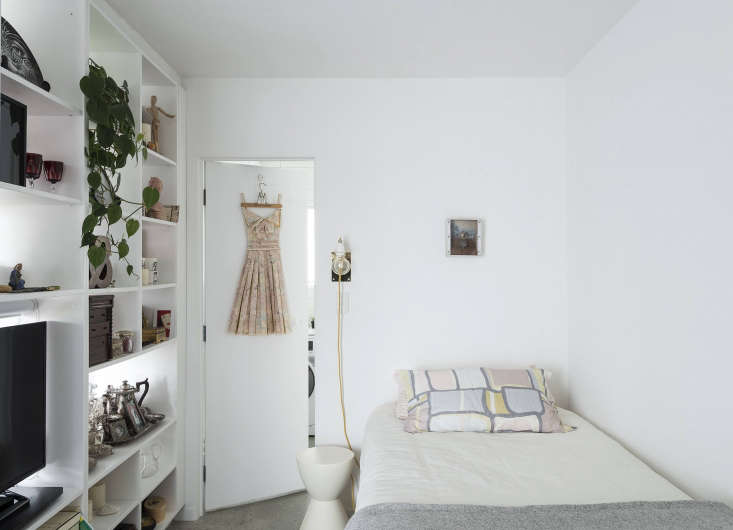 In the bedroom, a wall-mounted sconce found online provides reading light; aPrince Aha Stool by Kartell acts as a movable bedside table.