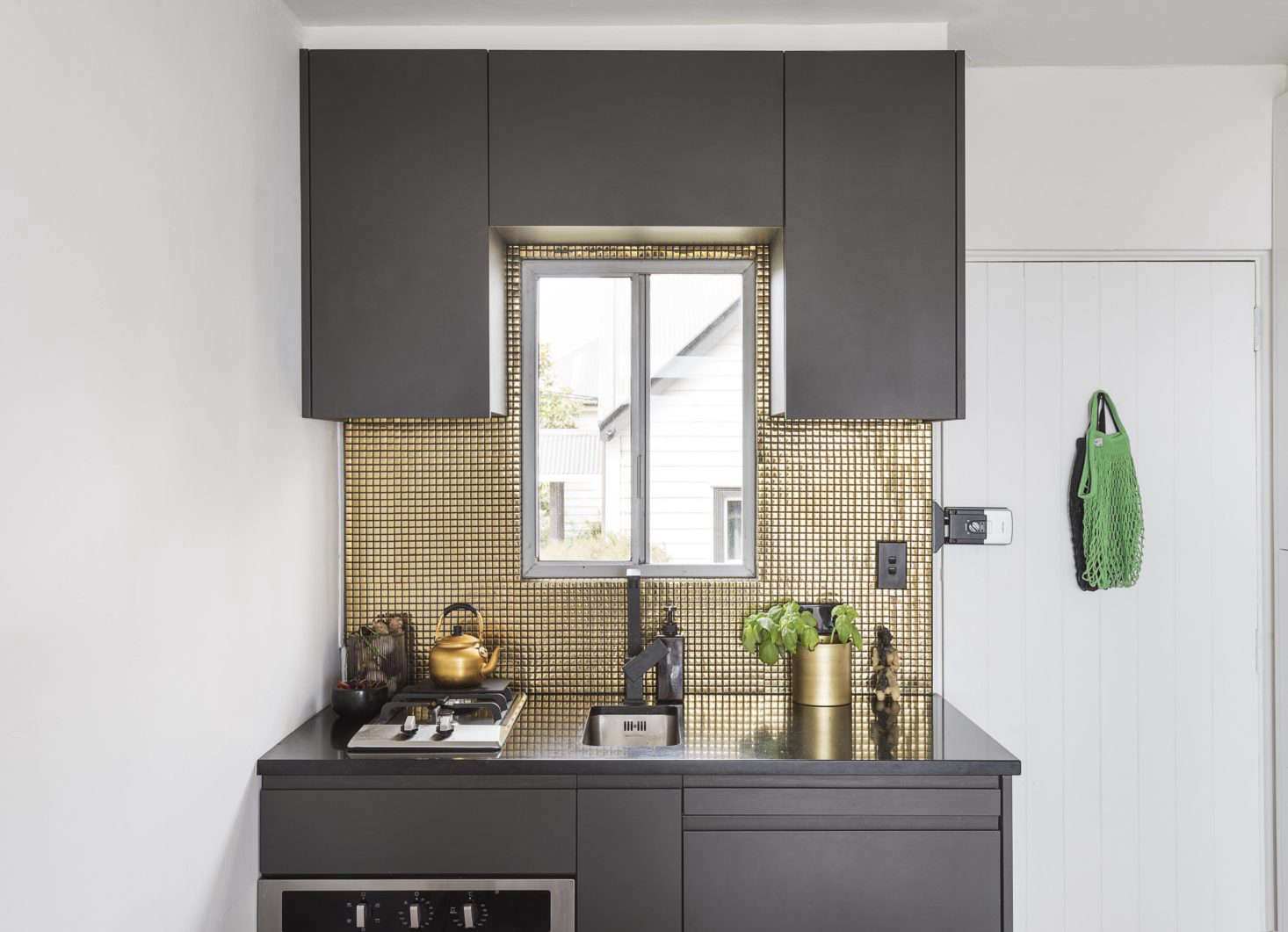 The new kitchenette is tiny but bold: Spath painted the cabinetry in Nero by Resene Paints; the tiles in the backsplash are from Tile Space in Auckland. In the spirit of tiny but efficient kitchens, Spath chose a small-space sink and range (see  Easy Pieces: Best Appliances for Small Kitchens).
