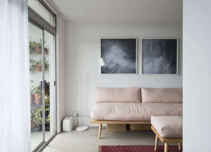 Despite its small footprint, the living room feels airy and open thanks to furniture with simple lines, a dark rug, and judicious edits: &#8