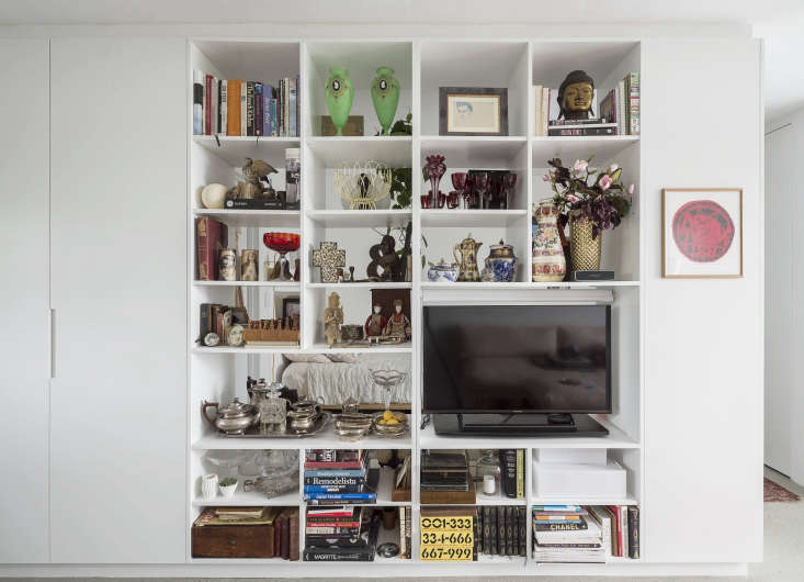 To create the illusion of a wall between living room and bedroom without building a wall, Spath added custom-built shelving. The client&#8