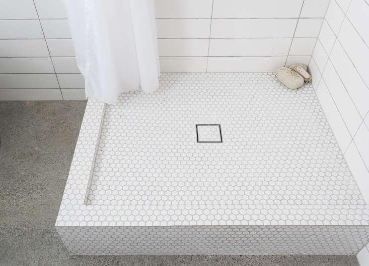 The new shower with sleek square drain; in the corner, a few pumice stones.