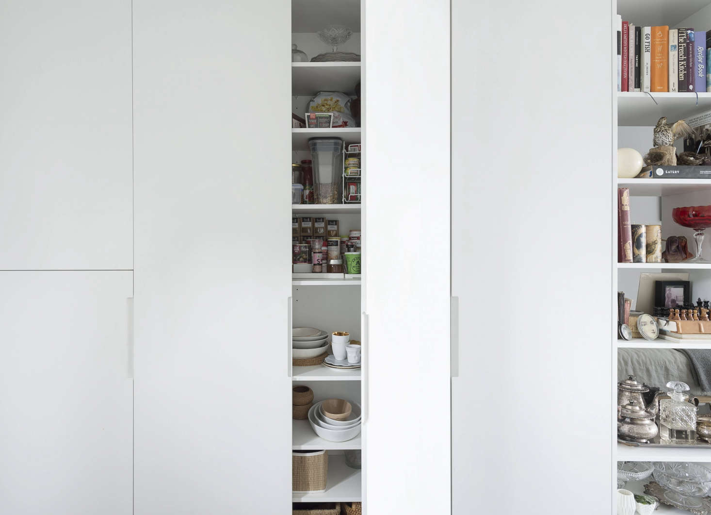 Floor-to-ceiling cabinets conceal dinnerware and dry goods.