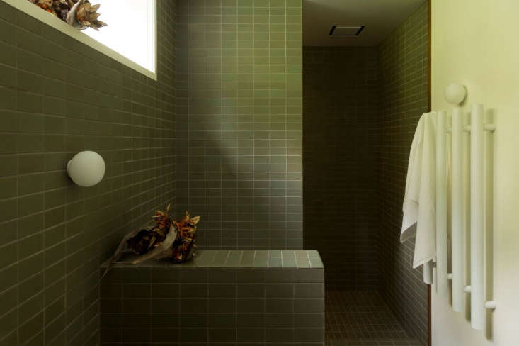 The bath's toilet is just beyond the half wall, and the shower—also fitted with Dornbracht Tara fixtures—is beyond that. The towel warmer is the DCS Modular Uno Round Rail in white. Flos Mini Glo Ball Wall Lights are used in both bathrooms.