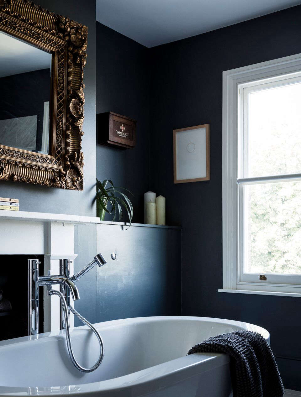 The en suite bathroom is dark and dramatic and painted in Down Pipe. Large mirrors and a window prevent it from being too dark.