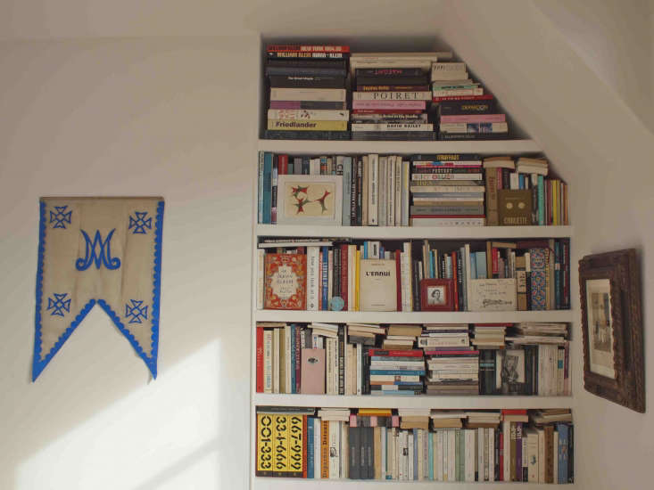Photographer Marie Hennecharts DIY Parisian Studio Apartment Makeover Floor to ceiling bookshelves are tucked into the end of the room that&#8\2\17;s partially open to the living area. The embroidered religious banner is another find from the Vanves flea market.