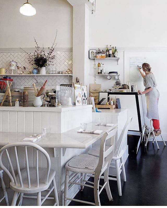 A long, low counter with mismatched white-painted chairs creates dining space around the open kitchen.