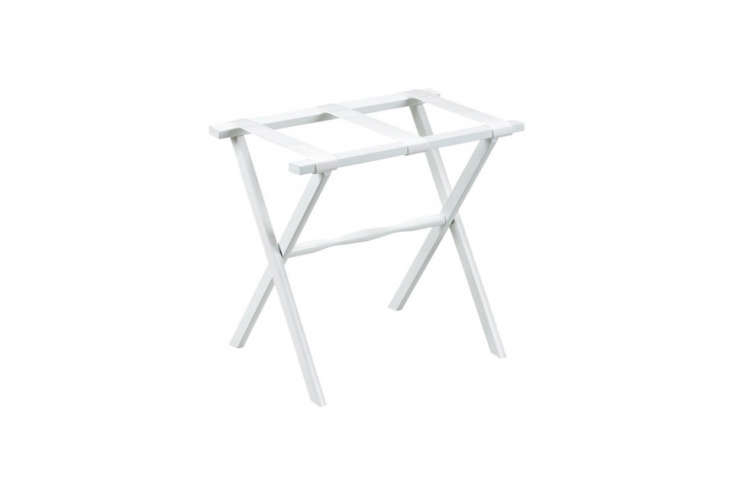 The Amalia Luggage Rack in painted white wood with white fabric straps is $loading=