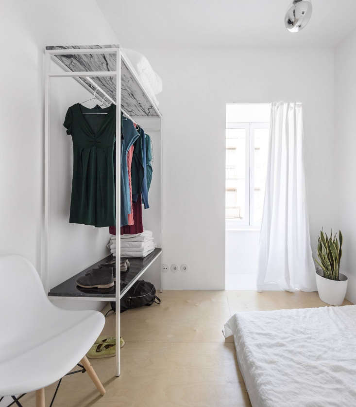 An open clothing storage unit makes use of two marble slabs to store shoes and folded items.