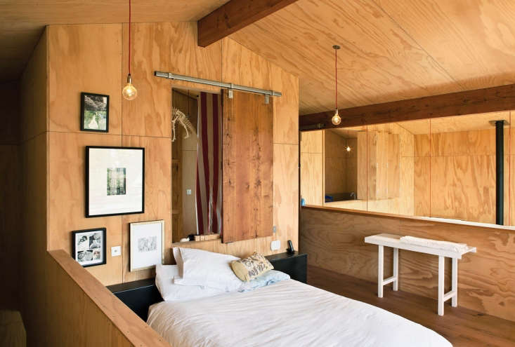 A sliding barn door made from oak floor boards becomes a feature in a bedroom clad in plywood, by architect Davor Popadich on Auckland&#8
