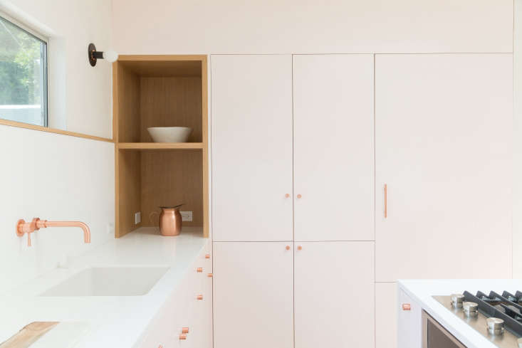 To keep the counters clear, the architects incorporated plenty of closed storage. The refrigerator is concealed behind a wall of flush cabinetry inset with an oak appliance nook.
