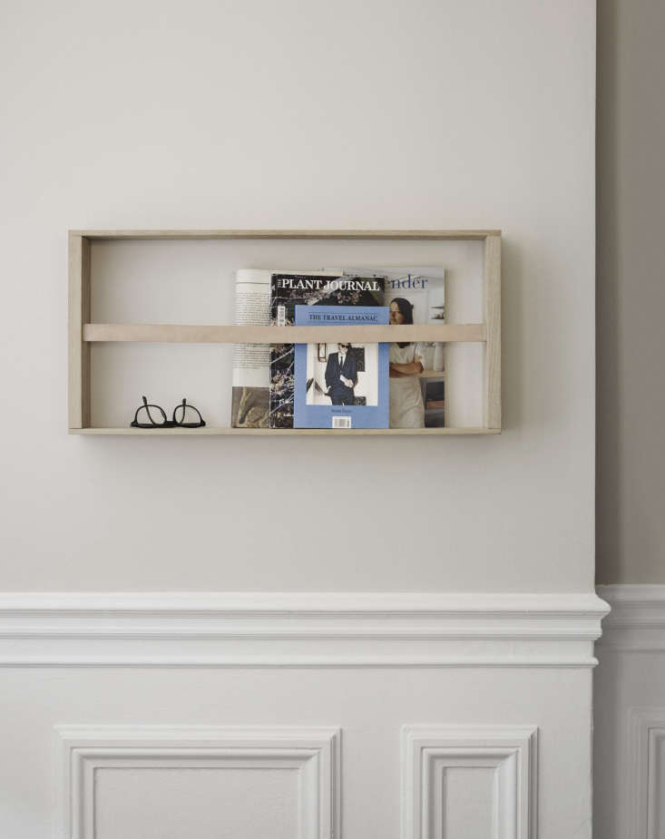 The oak and brassNorr Magazine Holder has a leather ribbon that holds books and periodicals in place (loading=