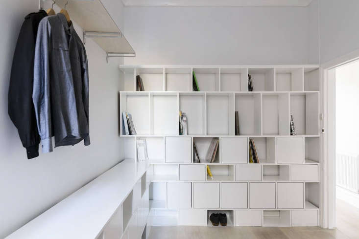 Not every bedroom needs a closet and chest of drawers. Henkell installed a wall of white MDF cubbies to give the eventual owner flexible storage space for &#8