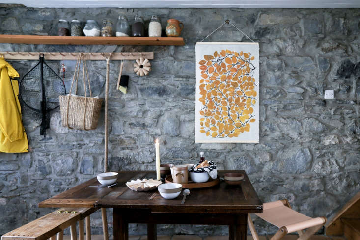 the dining table area is set off by an exposed stone wall hung with a superfolk 14