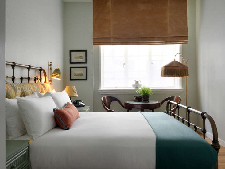 a guest room features an iron bed frame, velvet ochre colored shades, and a fri 10