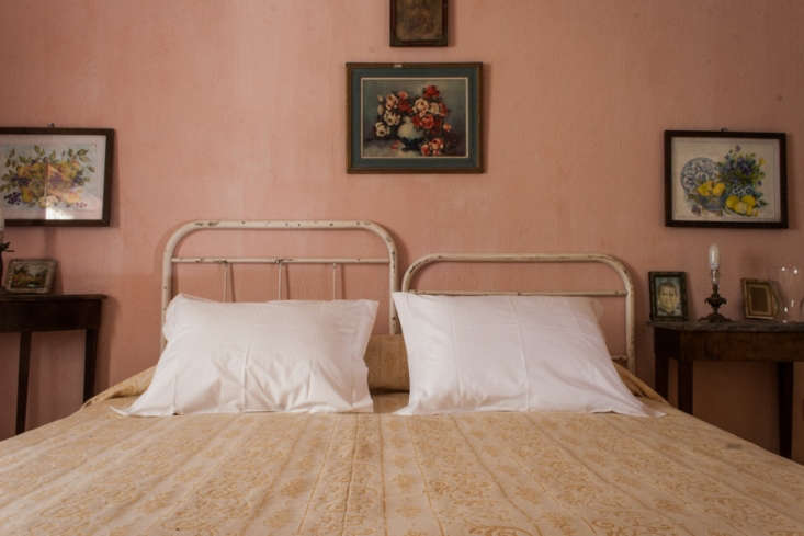 The Countryside House can be booked as a family suite of four bedrooms or as individual rooms. Shown here: one of the guest rooms, with charmingly mismatched iron headboards.