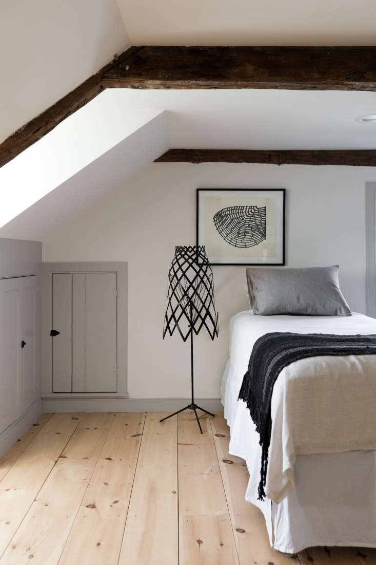in a narrow bedroom, esteves preserved the under eaves cabinets, which his moth 26