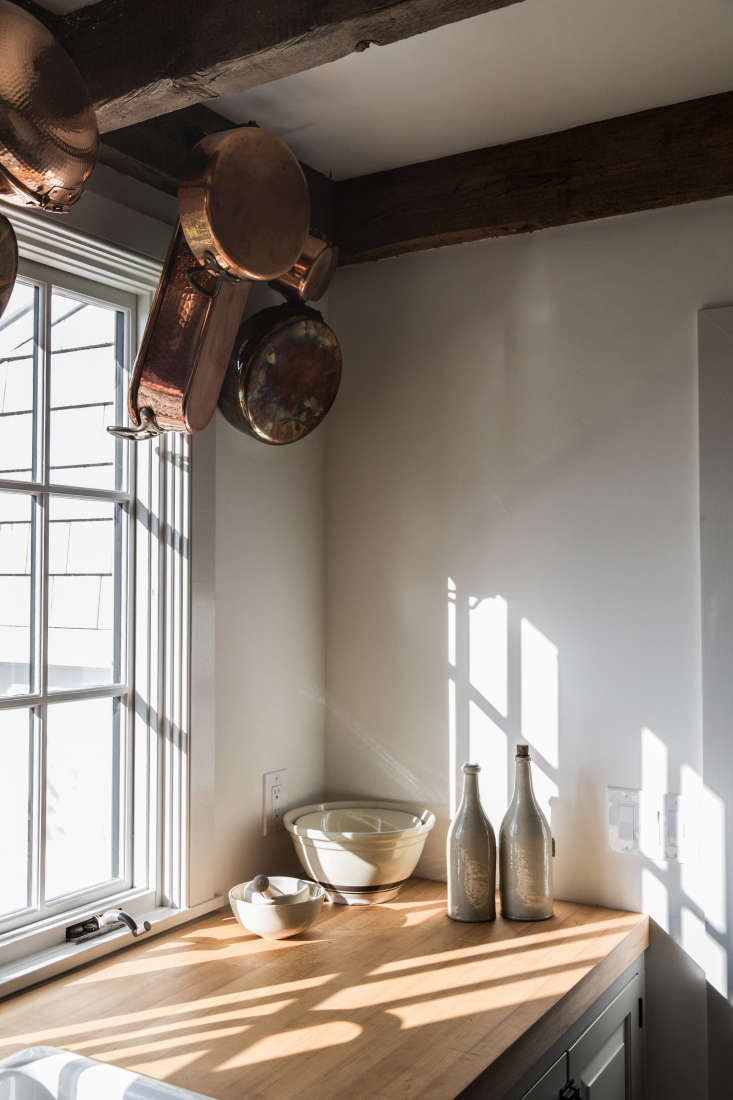 in another corner of the kitchen, copper pans hang from iron wall hooks affixed 12