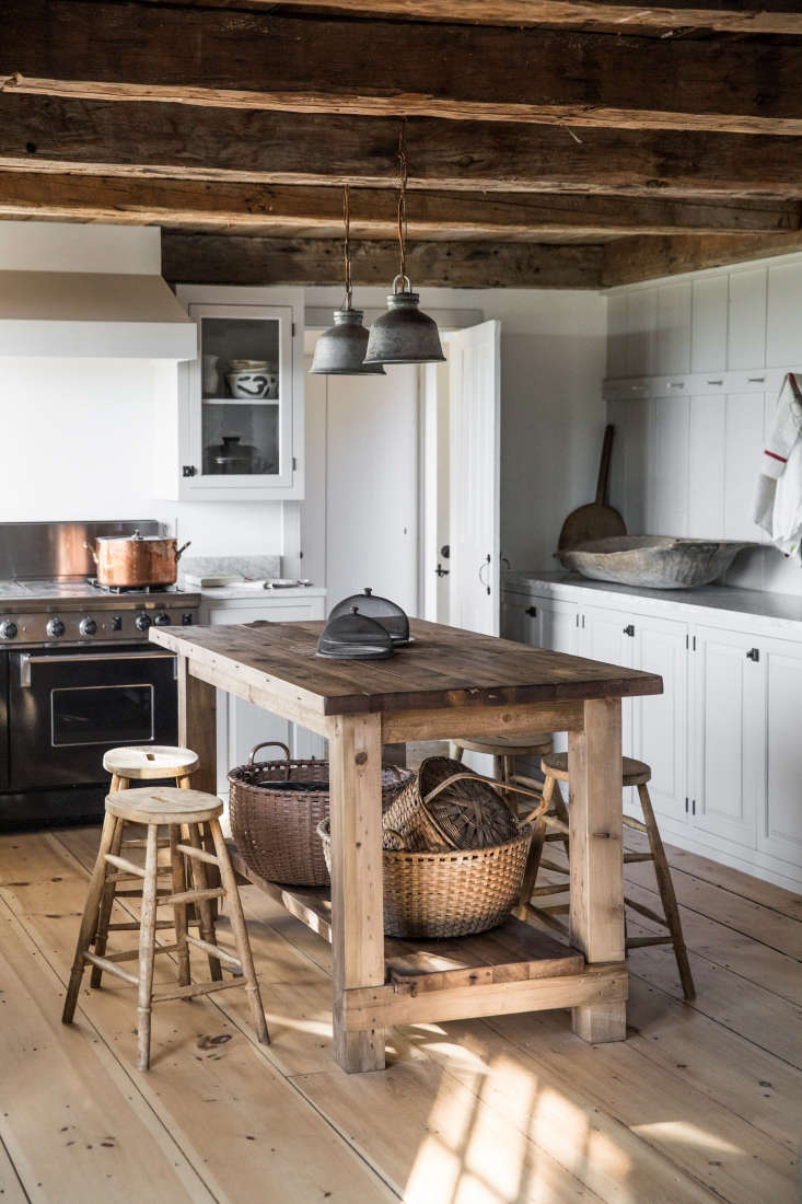 one side of the kitchen is lined with peg rails. the round baskets beneath the  13