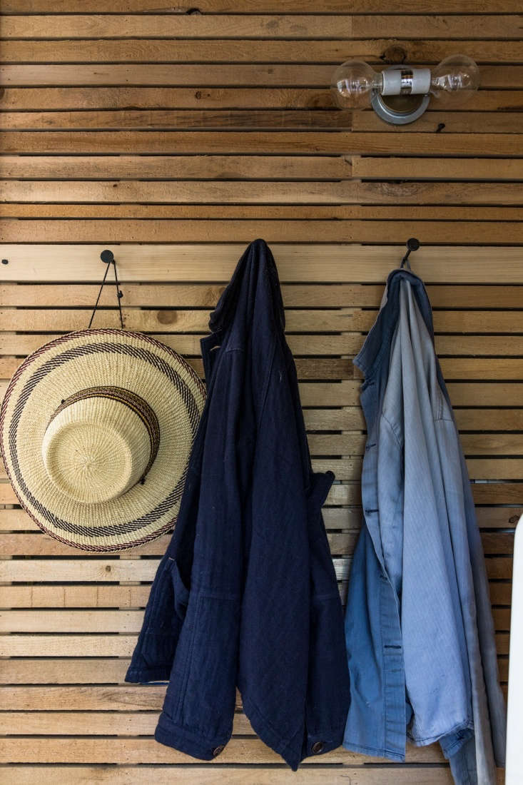 Work shirts hang on hooks from Sugar Tools in Camden, Maine. The pared-down lighting fixtures throughout the house are the U/loading=