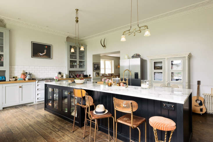 The kitchen is anchored by a large central island with cabinetry from deVOL&#8