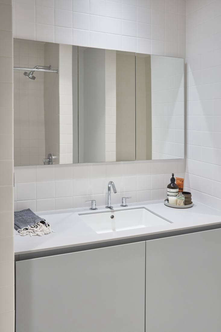 A bathroom with a Silver Gray Corian counter, a Kohler Stillness Bath Faucet, and a Hasami Gloss Gray Plate with Aesop products and Jen Pearson's Apothecary Matchstick Bottle.